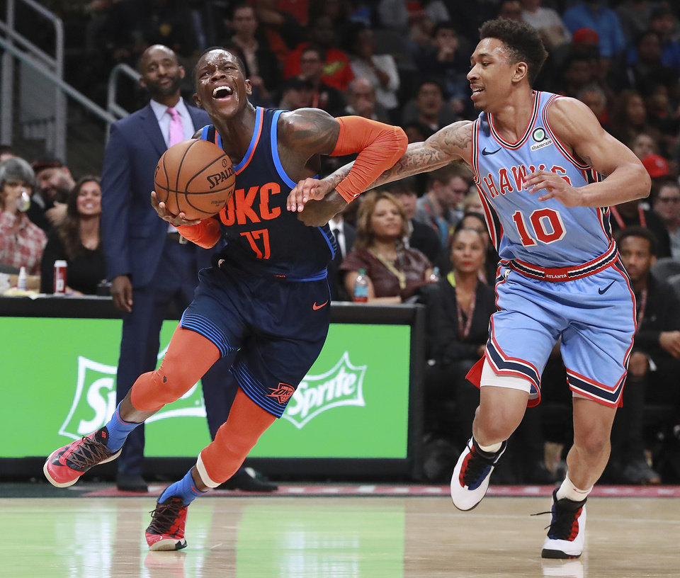 Photo - Atlanta Hawks guard Jaylen Adams (10) fouls Oklahoma City Thunder guard Dennis Schroder (17) during the second half of an NBA basketball game on Tuesday, Jan. 15, 2019, at State Farm Arena in Atlanta. (Curtis Compton/Atlanta Journal-Constitution via AP)
