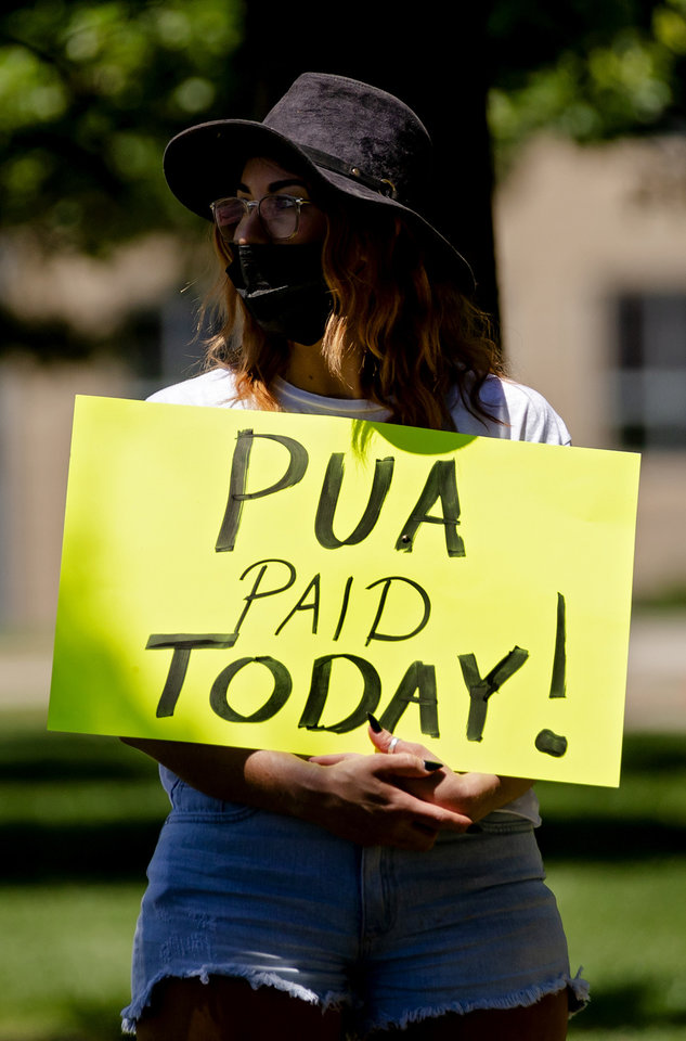 Photo - Daysha Jones, carries a sign as she gathers with other self-employed Oklahomans at the Oklahoma state Capitol to protest the lack of unemployment payments on Monday, May 18, 2020, in Oklahoma City, Okla..  [Chris Landsberger/The Oklahoman]