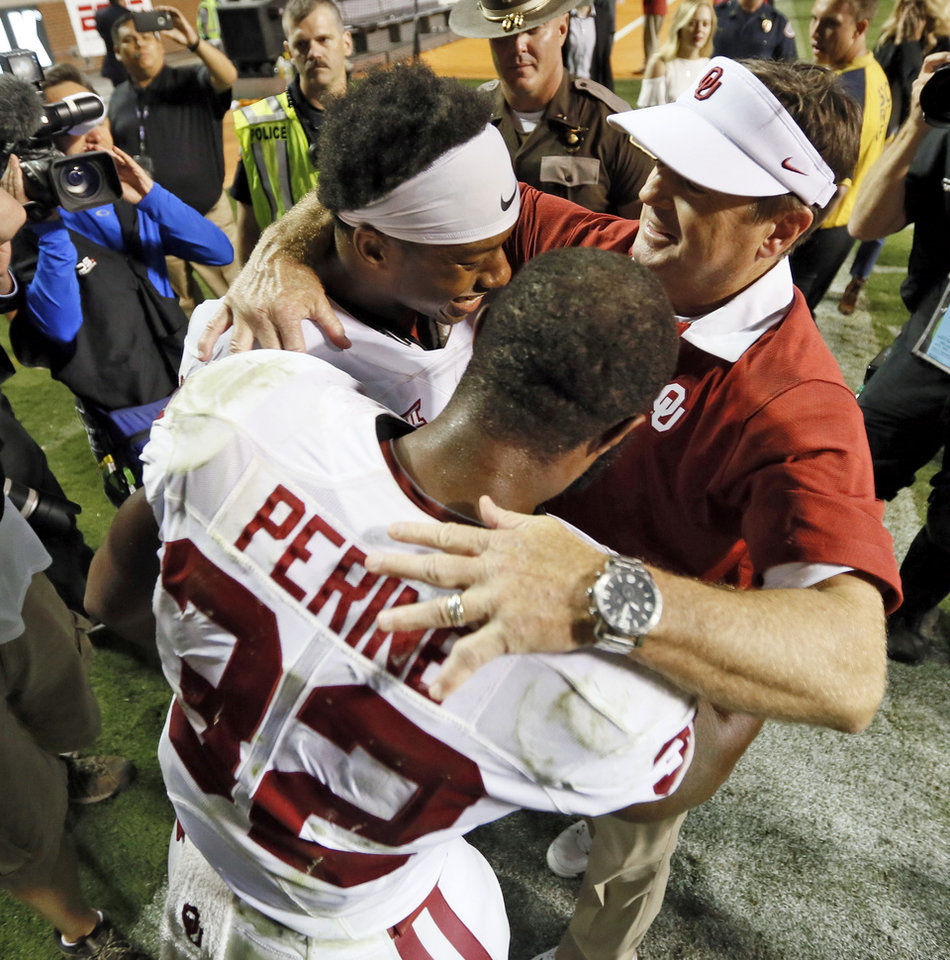 Photo - OU head coach Bob Stoops, right, celebrates with Oklahoma's Samaje Perine (32) and Joe Mixon (25) after the college football game between the Oklahoma Sooners (OU) and the Tennessee Volunteers at Neyland Stadium in Knoxville, Tennessee, Saturday, Sept. 12, 2015. OU won 31-24 in double overtime. Photo by Nate Billings, The Oklahoman