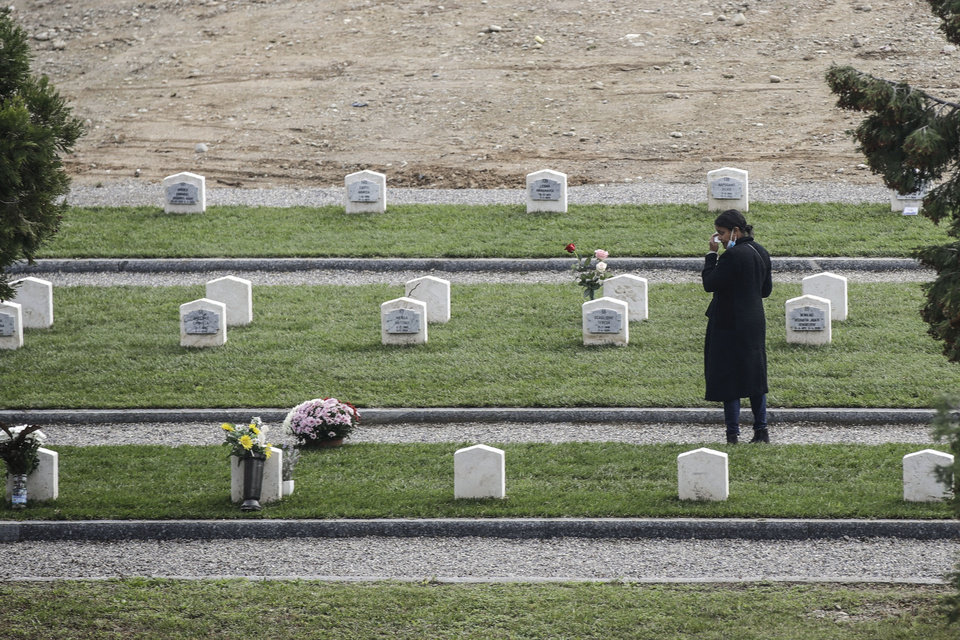 Photo -  A woman pays tribute to a tomb in the field 87 of the Maggiore cemetery, where several unclaimed victims of the COVID-19 pandemic were buried, in the day devoted to remembrance of the departed, in Milan, Italy, Monday, Nov. 2, 2020. (AP Photo/Luca Bruno)