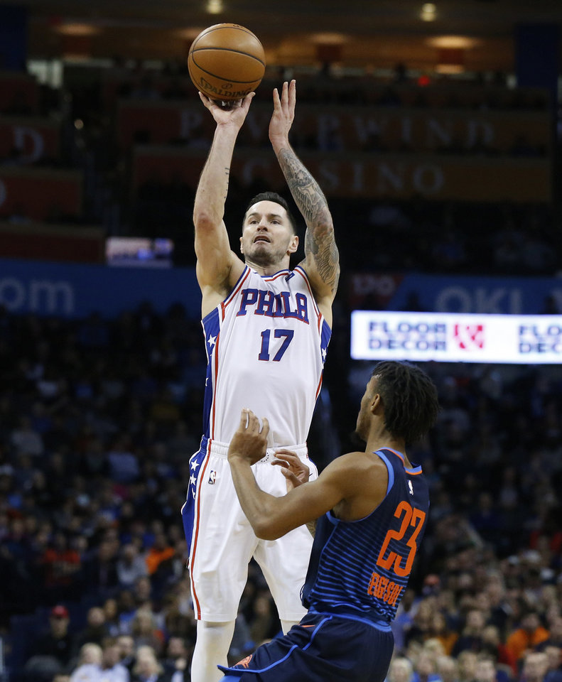 Photo - Philadelphia 76ers guard J.J. Redick (17) shoots over Oklahoma City Thunder guard Terrance Ferguson (23) during the first half of an NBA basketball game Thursday, Feb. 28, 2019, in Oklahoma City. (AP Photo/Sue Ogrocki)