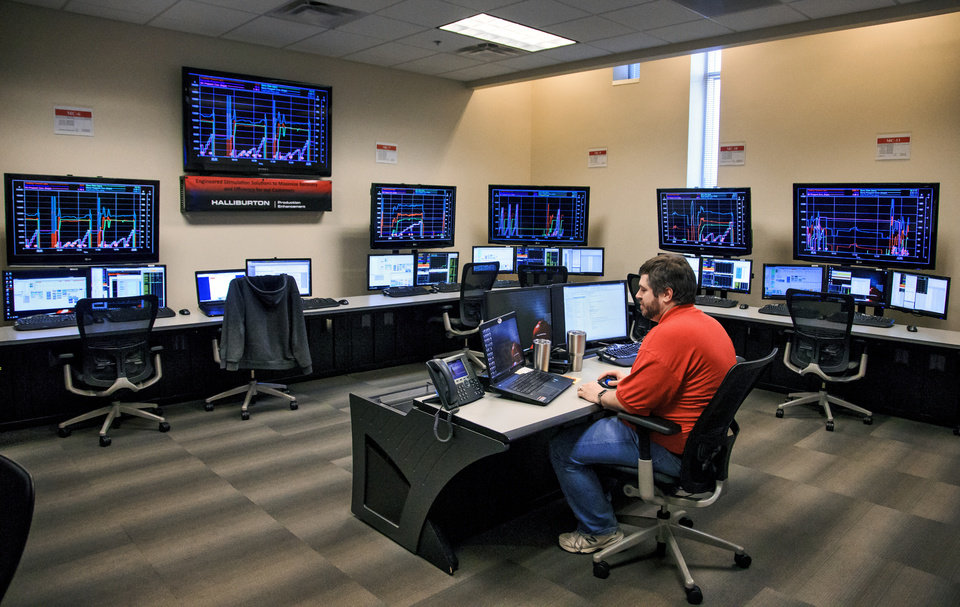 Photo -  James Dulin, Halliburton's senior technical professional, monitors the Remote Operations Command Center at Halliburton's regional control center for its hydraulic fracturing operations in El Reno. [Photo by Chris Landsberger, The Oklahoman]