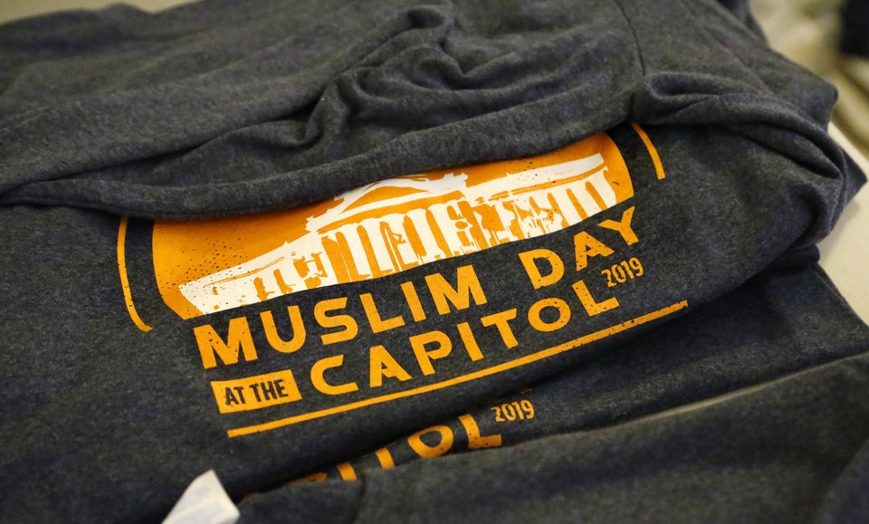 Photo - Silk-screened shirts commemorating Muslim Day at the Capitol are spread across a table for participants on the second floor rotunda at the Capitol. More than 100 participated in Muslim Day at the Capitol on Monday, March 4, 2019.  The annual event is sponsored by the Council on American-Islamic Relations-Oklahoma chapter. Interfaith supporters   held signs welcoming Muslim guests as they arrived at the Capitol. A man and a woman stood nearby, displaying placards expressing concerns about crimes committed by some Muslims in the recent past.   Photo by Jim Beckel, The Oklahoman.