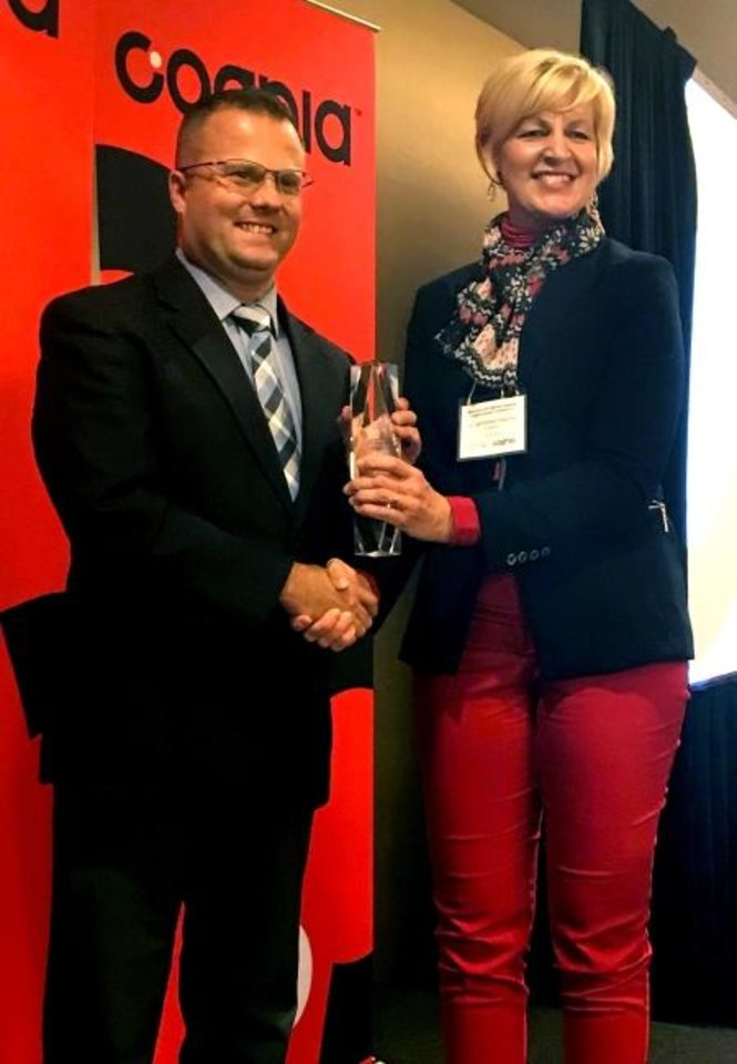 Photo -  Andrew Worthington, assistant principal of curriculum, testing and admissions at Bishop McGuinness Catholic High School, accepts the 2019 Values Driven Award of Excellence award from Lori Hopkins, Cognia regional director. [PHOTO PROVIDED]