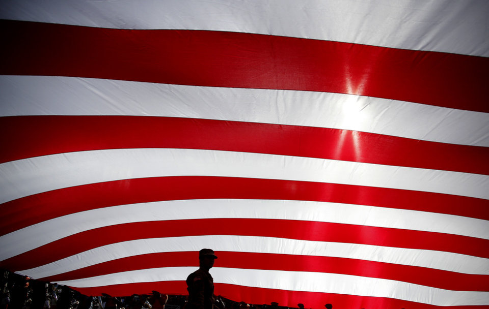 Photo - A member of the military stands under a large American flag during the college football game between the Oklahoma State University Cowboys and the Kansas Jayhawks at Boone Pickens Stadium in Stillwater, Okla., Saturday, Nov. 16, 2019. OSU won 31-13. [Sarah Phipps/The Oklahoman]