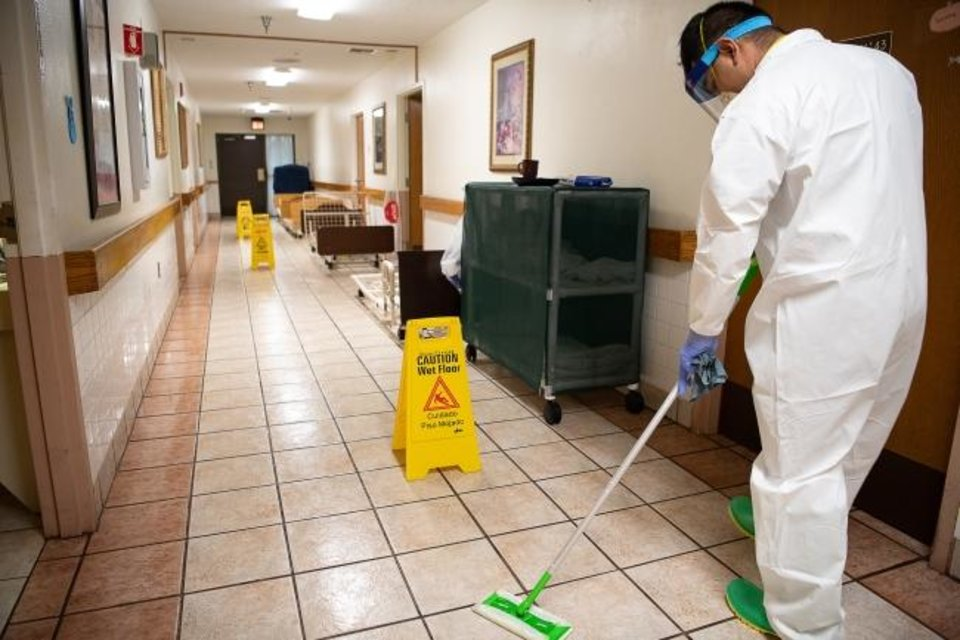 Photo -  An Oklahoma National Guardsman uses a cleaning solution to mop floors while disinfecting a long-term health care facility Wednesday in McAlester. [Tech. Sgt. Kasey M. Phipps/Oklahoma Air National Guard]