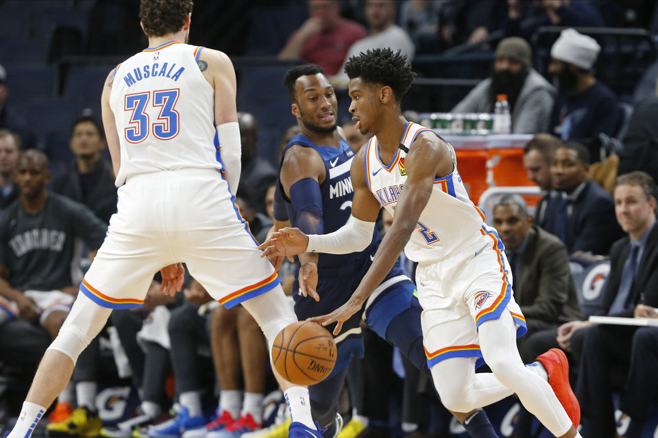 Photo - Oklahoma City Thunder's Mike Muscala, left, sets a pick for Shai Gilgeous-Alexander, right, of Canada as he drives past Minnesota Timberwolves' Josh Okogie of Nigeria in the first half of an NBA basketball game Monday, Jan. 13, 2020, in Minneapolis. (AP Photo/Jim Mone)
