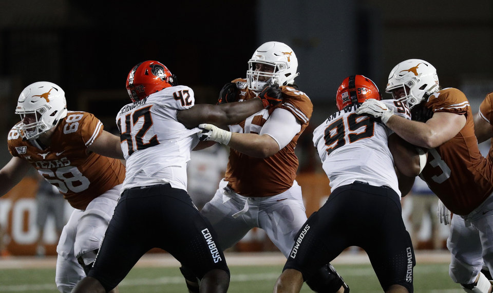 Photo - Texas offensive lineman Zach Shackelford (56) battles with Oklahoma State defensive tackle Jayden Jernigan (42) during the second half of an NCAA college football game Saturday, Sept. 21, 2019, in Austin, Texas. (AP Photo/Eric Gay)