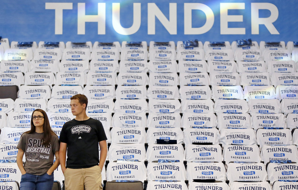 Photo - A pair of Spurs fans watch the teams warm up before Game 4 of the Western Conference semifinals between the Oklahoma City Thunder and the San Antonio Spurs in the NBA playoffs at Chesapeake Energy Arena in Oklahoma City, Sunday, May 8, 2016. Photo by Nate Billings, The Oklahoman