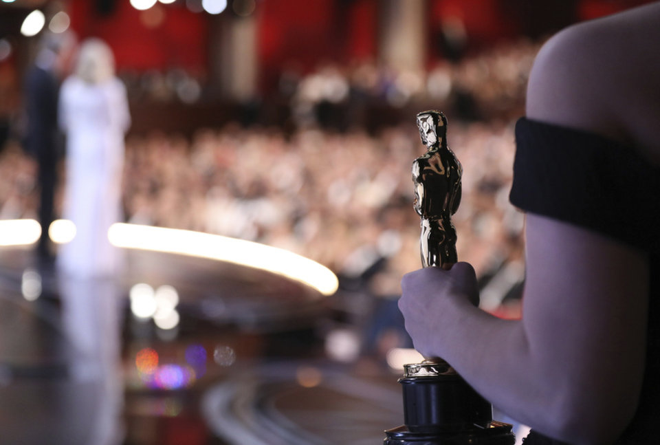 Photo - One of the best picture Oscar statuettes appears off stage as Warren Beatty and Faye Dunaway announce the best picture winner at the Oscars on Sunday, Feb. 26, 2017, at the Dolby Theatre in Los Angeles. (Photo by Matt Sayles/Invision/AP)