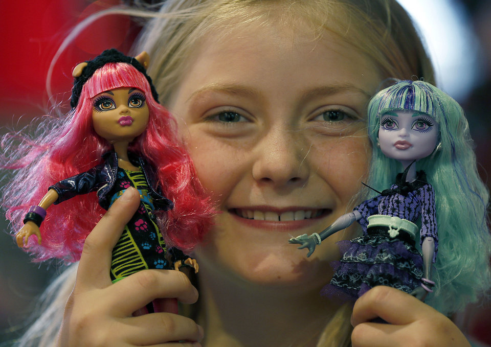 Photo - Tegan, 9, poses with Monster High Dolls as part of a Christmas toy preview at the toy store Hamleys June 27 in London. (AP Photo/Frank Augstein)  Frank Augstein - AP