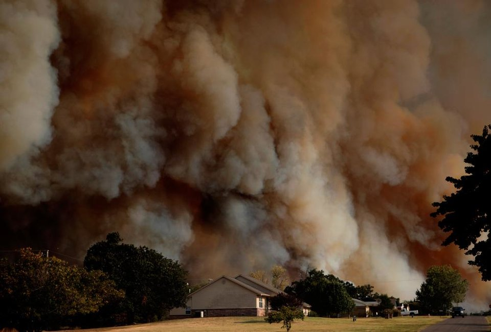 Photo -  Smoke surrounds home in Luther, Okla.,  during a large wildfire Friday, Aug. 3, 2012. Photo by Sarah Phipps, The Oklahoman