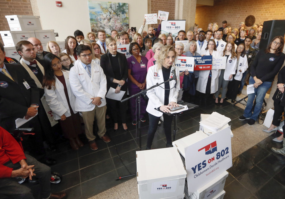 Photo - Ashton Gores, a medical student and volunteer with Yes on 802, speaks in front of Medicaid expansion supporters before they delivered petitions for state question 802 to the Oklahoma Secretary of State's office in Oklahoma City, Thursday, Oct. 24, 2019. [Nate Billings/The Oklahoman]