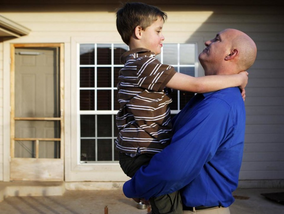 Photo -  Eric Littleton holds his son Solomon Littleton, 7, at their home, 17313 Zinc Drive, in Edmond, Okla., Thursday, December 16, 2010. Solomon Littleton has a neurological disorder that gives him symptoms similar to autism and Alzheimer's disease. Photo by Nate Billings, The Oklahoman ORG XMIT: KOD