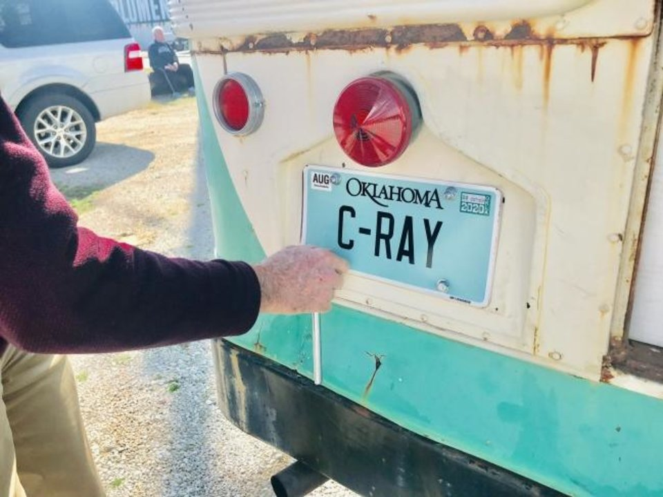 Photo -  Ed Neuenschwander places a specialty license plate on a vintage Straight Shooters bus to pay homage to the youth ministry's beloved founder Clifford Ray. [Carla Hinton/The Oklahoman]