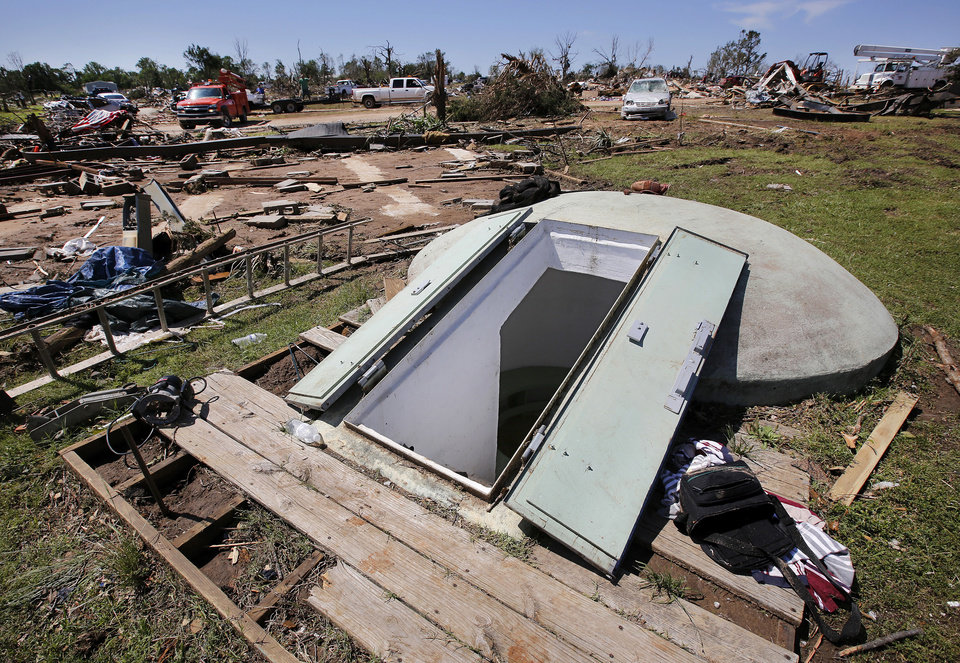 Photo - This storm shelter is where Bill Stoops and three other adults and dogs sought safety from a tornado that destroyed his home and many other houses in Steelman Estates in Bethel Acres on Sunday, May 19, 2013. His double-wide manufactured home used to be on the empty spot behind the shelter.  Photo  by Jim Beckel, The Oklahoman.