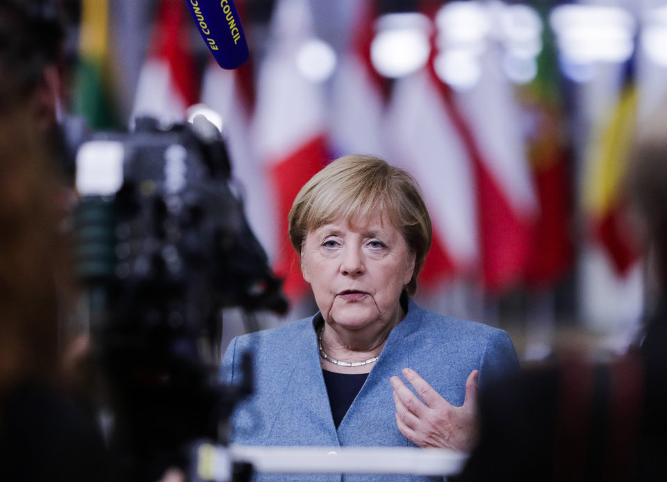 Photo -  German Chancellor Angela Merkel speaks to the media during departures at an EU summit in Brussels, Thursday, Oct. 15, 2020. European Union leaders met in person for the first day of a two-day summit, amid the worsening coronavirus pandemic, to discuss topics ranging from Brexit to climate and relations with Africa. (Olivier Hoslet, Pool via AP)