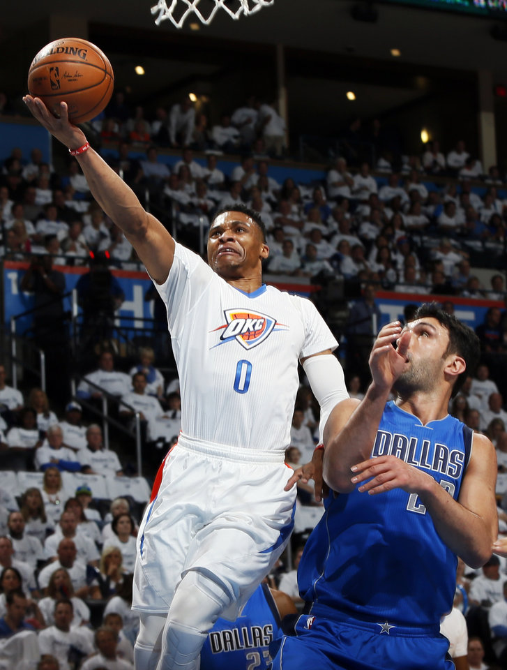 Photo - Oklahoma City's Russell Westbrook (0) takes the ball to the hoop past Dallas' Zaza Pachulia (27) during Game 2 of the first round series between the Oklahoma City Thunder and the Dallas Mavericks in the NBA playoffs at Chesapeake Energy Arena in Oklahoma City, Monday, April 18, 2016. Photo by Nate Billings, The Oklahoman