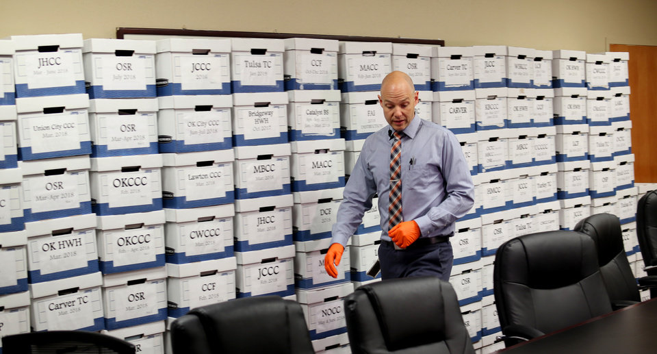 Photo -  Corrections Department spokesman Matt Elliott shows cellphones Thursday that have been confiscated in Oklahoma prisons. The boxes in the background are all full of phones. [Doug Hoke/The Oklahoman]