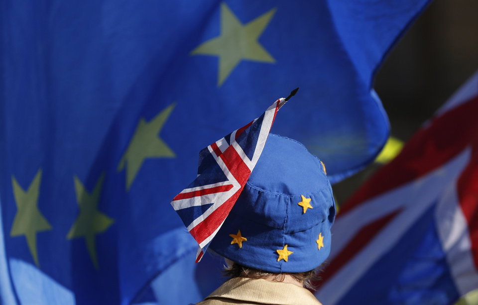 Photo -  FILE - In this Oct. 16, 2018, file photo, a pro-EU demonstrator wears an EU flag styled as a hat, with a British Union flag pinned to it in London. With Brexit due on Oct. 31, 2019 and a costly no-deal a possible outcome, experts still do not know, or are reluctant to say, exactly what checks are likely at the Irish border. Nevertheless, British Prime Minister Boris Johnson remains convinced that a Brexit deal can be sealed with the EU in a few weeks. (AP Photo/Alastair Grant, File)