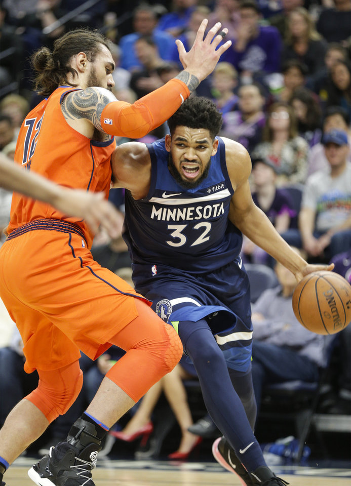 Photo - Minnesota Timberwolves center Karl-Anthony Towns (32) drives against Oklahoma City Thunder center Steven Adams, of New Zealand, (12) during the first half of a NBA basketball game Sunday, April 7, 2019, in Minneapolis. (AP Photo/Paul Battaglia)