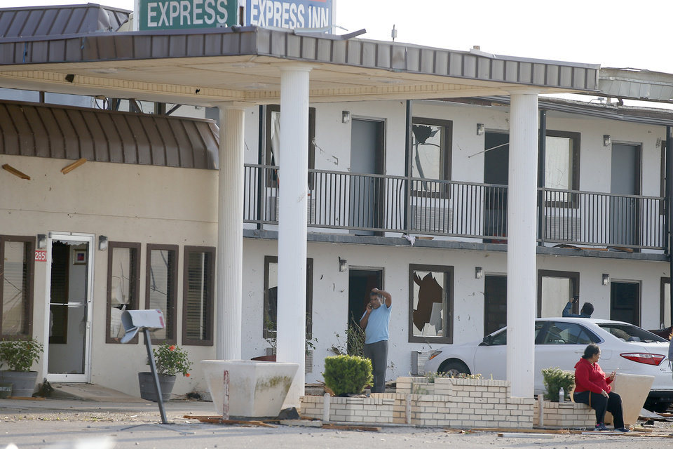 Photo - People stand outside the Economy Express Inn after a tornado damaged it the previous night in El Reno, Okla., Sunday, May 26, 2019. [Bryan Terry/The Oklahoman]