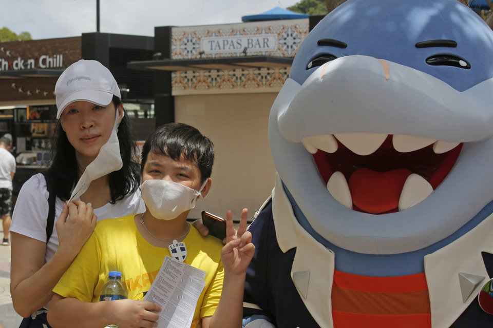 Photo -  A woman takes off her face mask for a photograph at the Ocean Park amusement park in Hong Kong, Saturday, June 13, 2020. Hong Kong's Ocean Park reopened Saturday after nearly four months of closure due to the coronavirus pandemic. The animal and nature-themed attraction combines pandas, penguins, roller coasters and other rides, and has been a Hong Kong icon since its opening in 1977. (AP Photo/Kin Cheung)