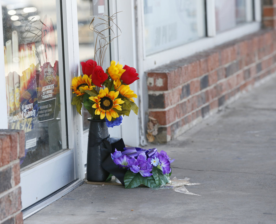 Flowers sit in front of the doors to Kim's Country Mart, where a clerk was killed early Saturday morning, in Anadarko, Okla., Monday, Jan. 25, 2016.