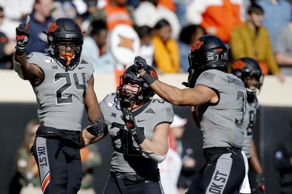 Photo -  Oklahoma State's Jarrick Bernard, left, celebrates a play in the third against Kansas on Saturday. OSU won 31-13. [Sarah Phipps/The Oklahoman]
