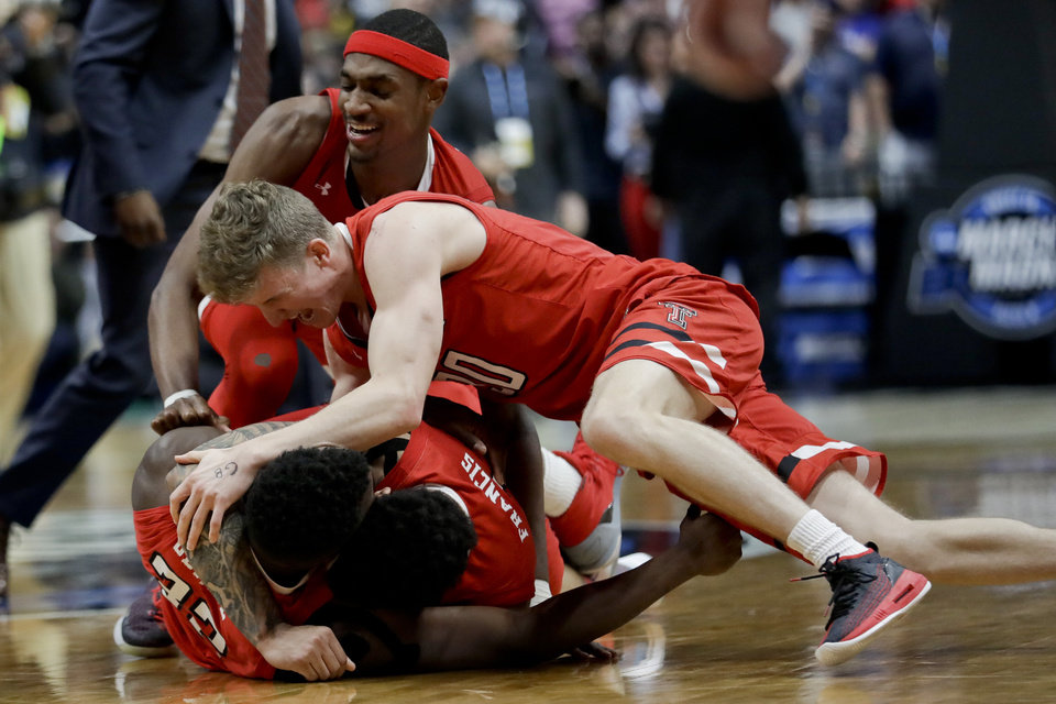 Photo - Texas Tech players, including Norense Odiase, bottom left, Brandone Francis, bottom right, and Tariq Owens, top, with headband, celebrate after a win against Gonzaga during the West Regional final in the NCAA men's college basketball tournament Saturday, March 30, 2019, in Anaheim, Calif. Texas Tech won 75-69. (AP Photo/Marcio Jose Sanchez)