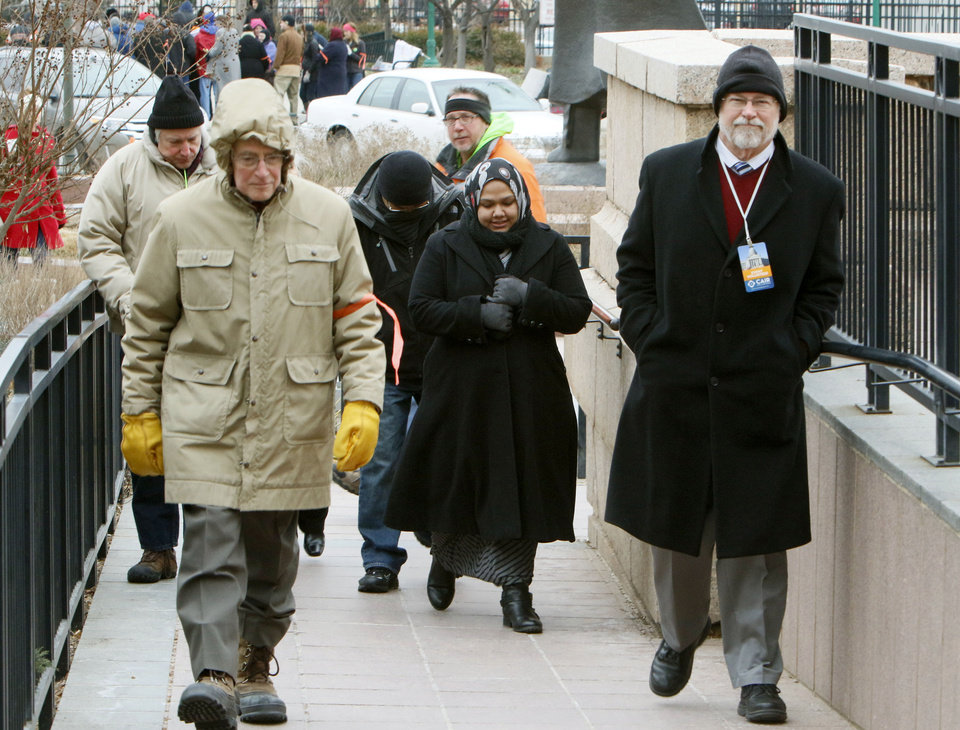 Photo -  Volunteers from the interfaith community escort Muslims past protesters as Muslims gather Feb. 27, 2015 at the state Capitol for