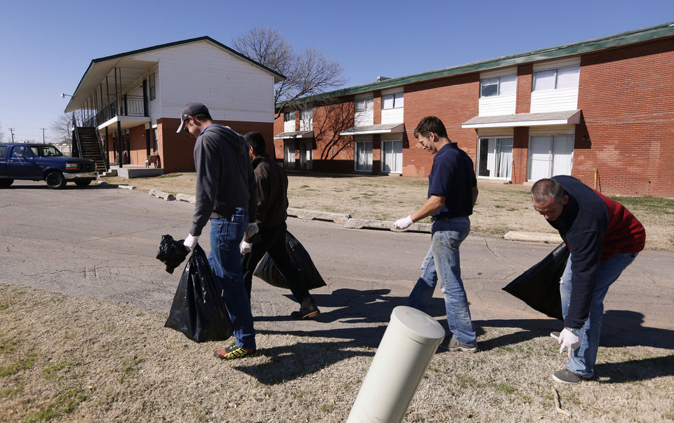 Photo -  Volunteers clean up trash in south Oklahoma City as part of an Adopt-a-Block outreach program organized by the Oklahoma City Dream Center. [Photo by Paul Hellstern, The Oklahoman]