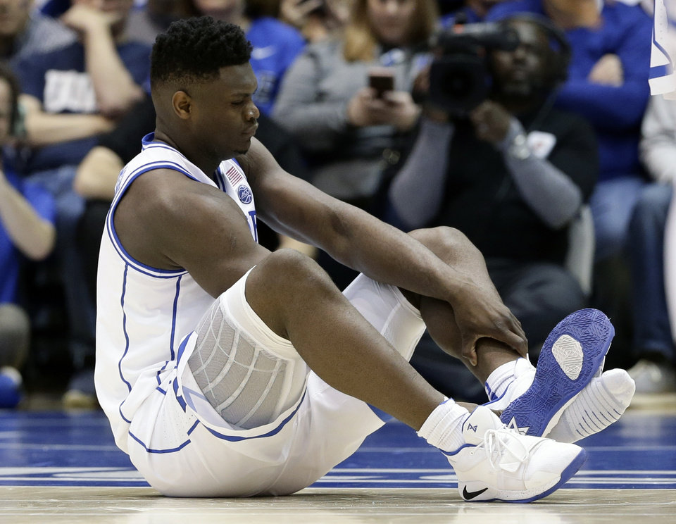 Photo -  As his Nike shoe blew out, Duke's Zion Williamson sprained his right knee on the first possession of what became top-ranked Duke's 88-72 loss to No. 8 North Carolina on Wednesday. [AP Photo/Gerry Broome]