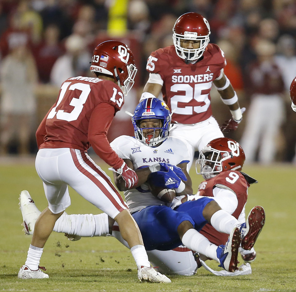 Photo - Oklahoma's Kenneth Murray (9) brings down Kansas' Jeremiah Booker (88) between Oklahoma's Tre Norwood (13) and Justin Broiles (25) during a college football game between the University of Oklahoma Sooners (OU) and the Kansas Jayhawks (KU) at Gaylord Family-Oklahoma Memorial Stadium in Norman, Okla., Saturday, Nov. 17, 2018. Photo by Bryan Terry, The Oklahoman