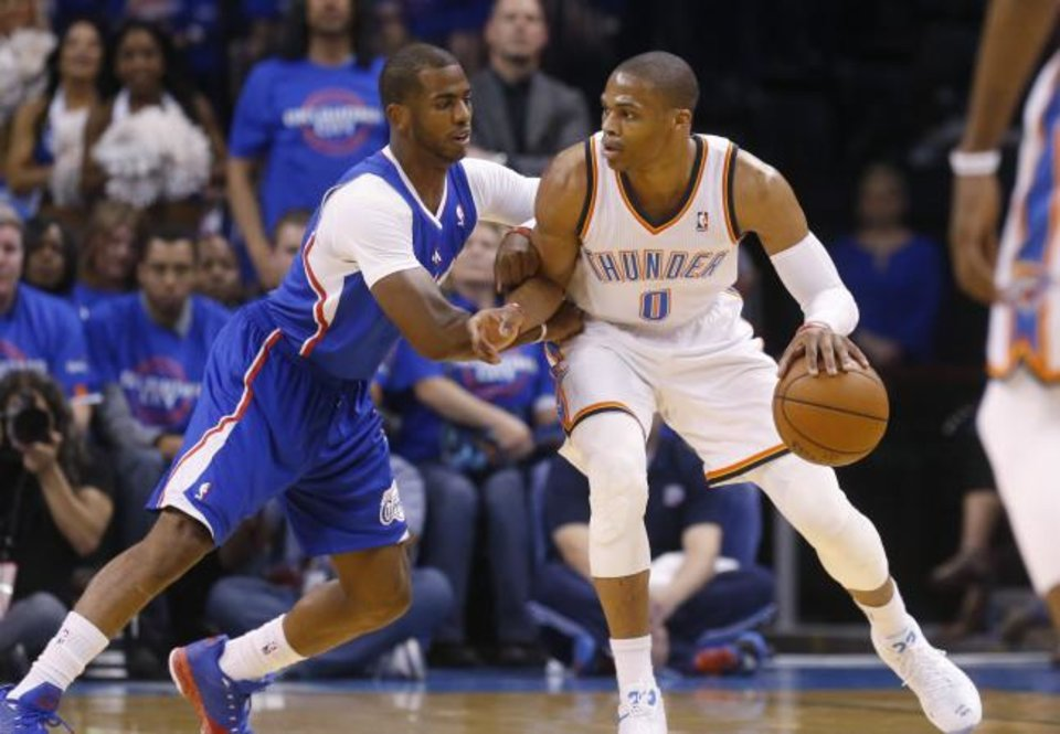 Photo -  In this May 5, 2014 file photo, Oklahoma City Thunder guard Russell Westbrook (0) drives against Los Angeles Clippers guard Chris Paul (3). Paul is returning to Oklahoma City after being traded from Houston for Westbrook. [AP Photo/Sue Ogrocki]