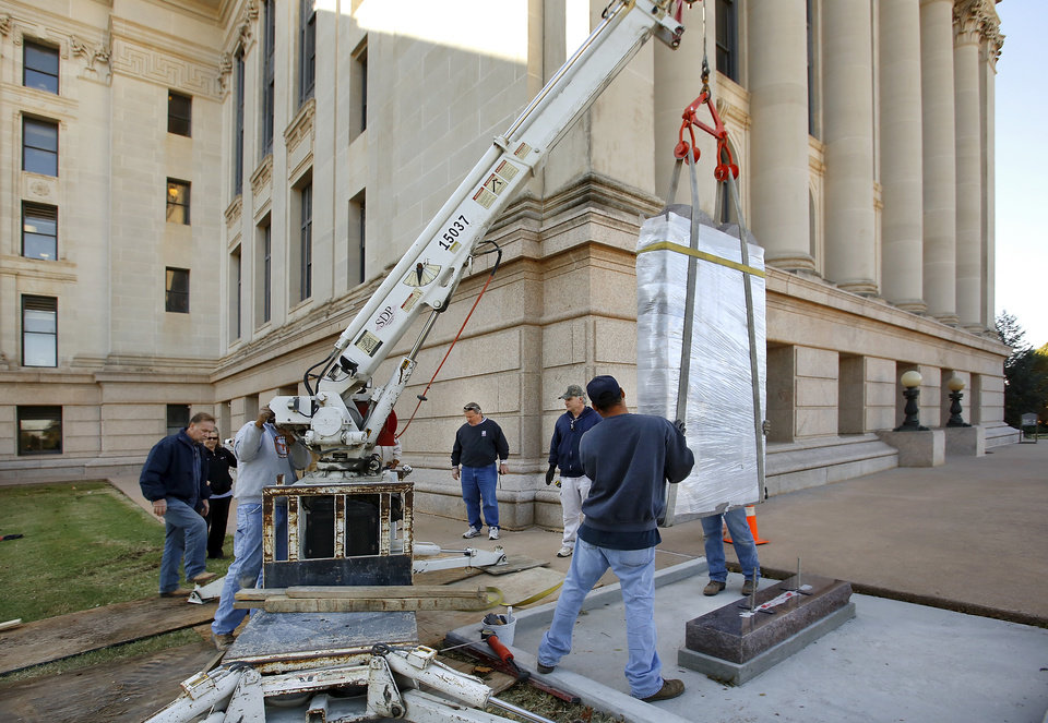 Photo - Workers move a granite monument of the Ten Commandments into position before lowering it onto its base on the north side of the state Capitol grounds Thursday morning, Nov. 15, 2012.  Photo by Jim Beckel, The Oklahoman