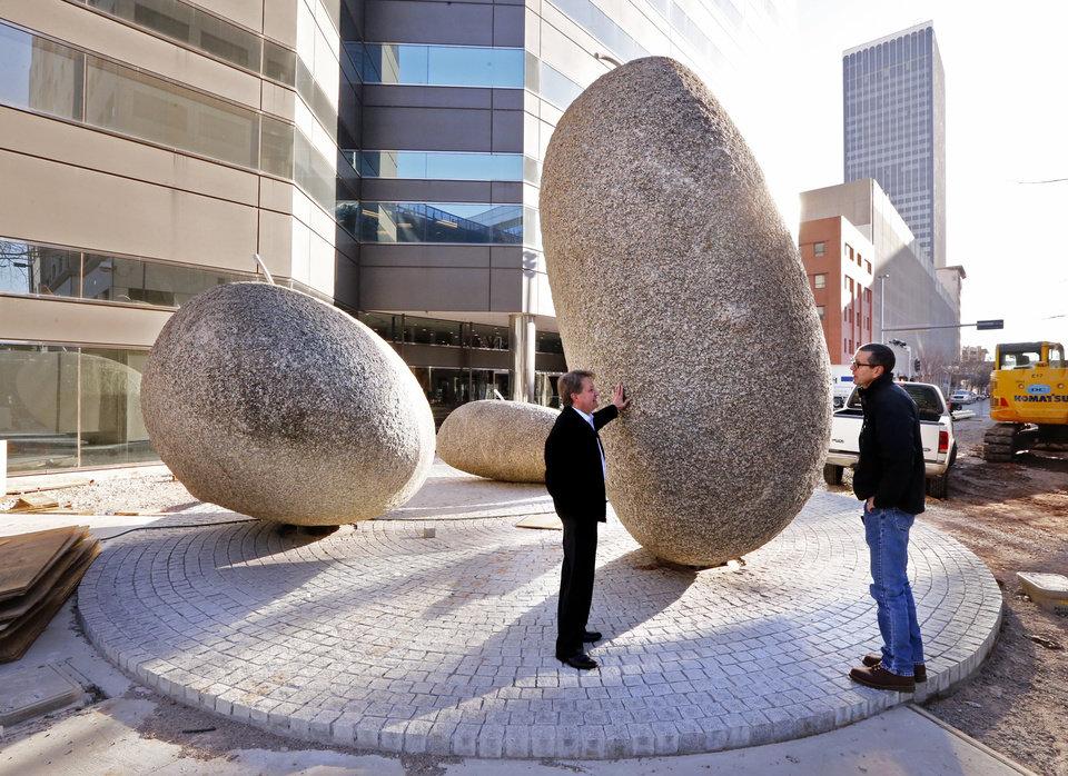 Photo -  Scott Howard, left, landscape architect, and Mike Clark, senior project manager for Oklahoma City's Public Works Department, show off huge rocks that are part of the downtown Pedestrian Plaza project.