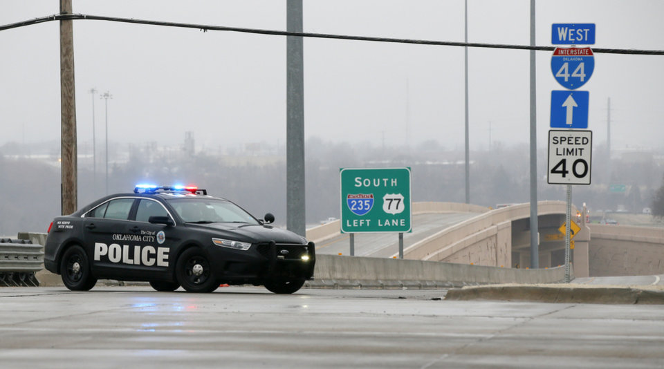 Photo - An Oklahoma City police car blocks the entrance ramp to westbound I-44 and southbound I-235 at NW 63rd during freezing rain in Oklahoma City, Wednesday, Feb. 27, 2019. by Nate Billings, The Oklahoman