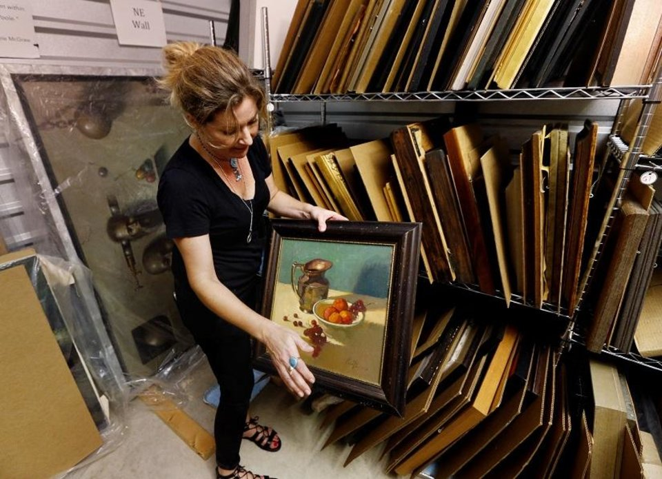 Photo - Nicole Poole sorts through art created by her father the late O. Gail Poole in a storage unit on Tuesday, July 5, 2016, in Norman, Okla. [The Oklahoman Archives photo]