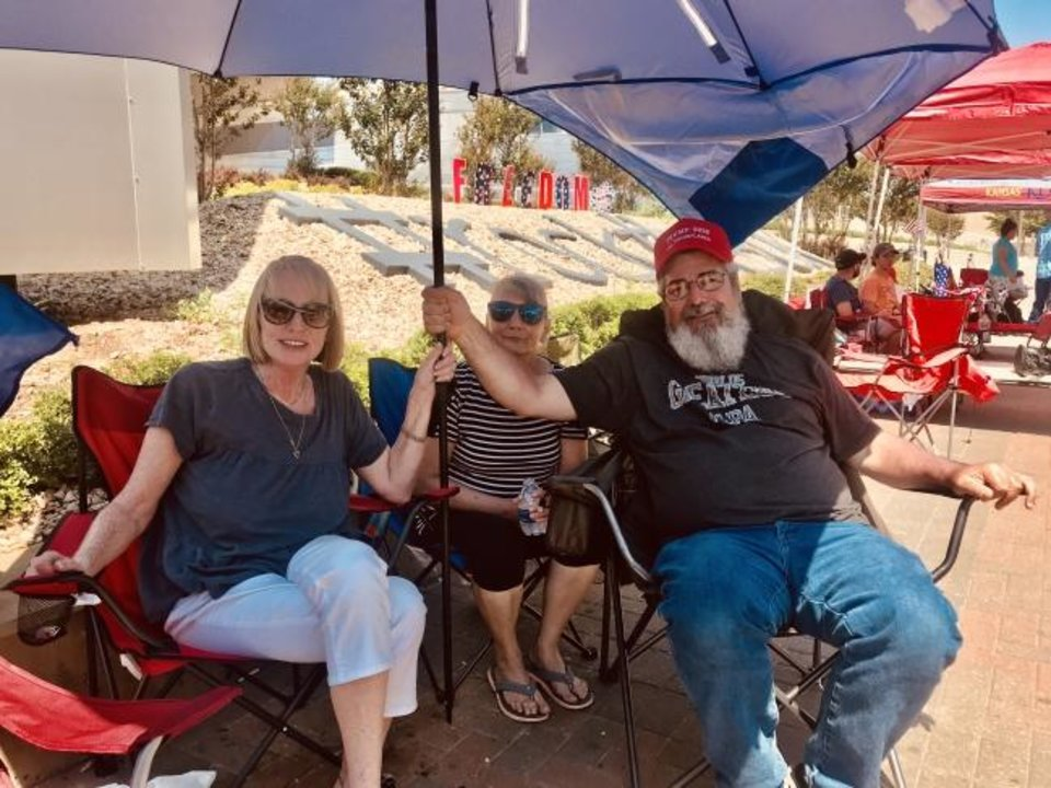 Photo -  Early bird Trump supporters Robin Stites and Angela Cox, both of Sallisaw, and James Massery of Preston sit under an umbrella on Wednesday outside the BOK Center at 200 S Denver in Tulsa. [Carla Hinton/The Oklahoman]