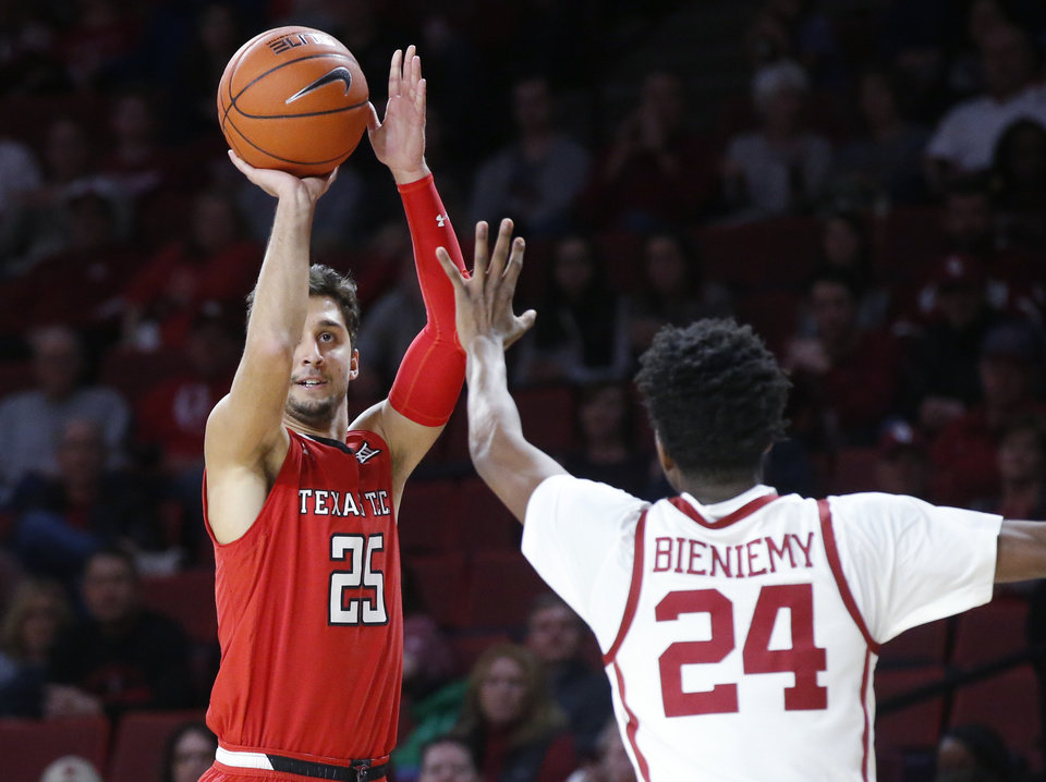 Photo - Texas Tech guard Davide Moretti (25) shoots as Oklahoma guard Jamal Bieniemy (24) defends in the first half of an NCAA college basketball game in Norman, Okla., Saturday, Feb. 9, 2019. (AP Photo/Sue Ogrocki)