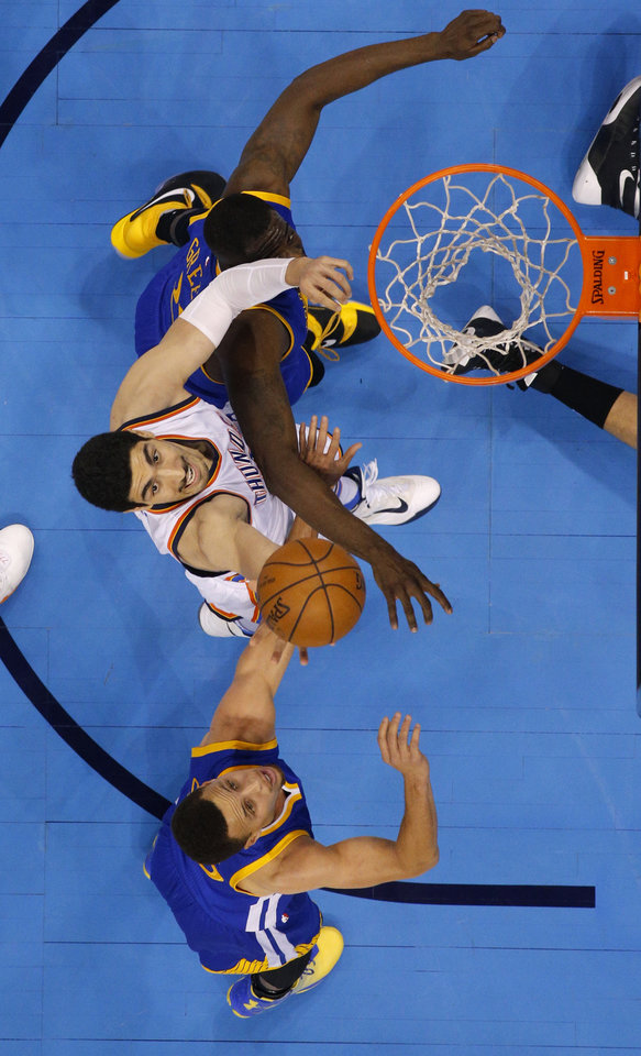 Photo - Oklahoma City's Enes Kanter (11) tips the ball from between Golden State's Draymond Green (23) and Stephen Curry (30) during Game 3 of the Western Conference finals in the NBA playoffs between the Oklahoma City Thunder and the Golden State Warriors at Chesapeake Energy Arena in Oklahoma City, Sunday, May 22, 2016. Photo by Bryan Terry, The Oklahoman