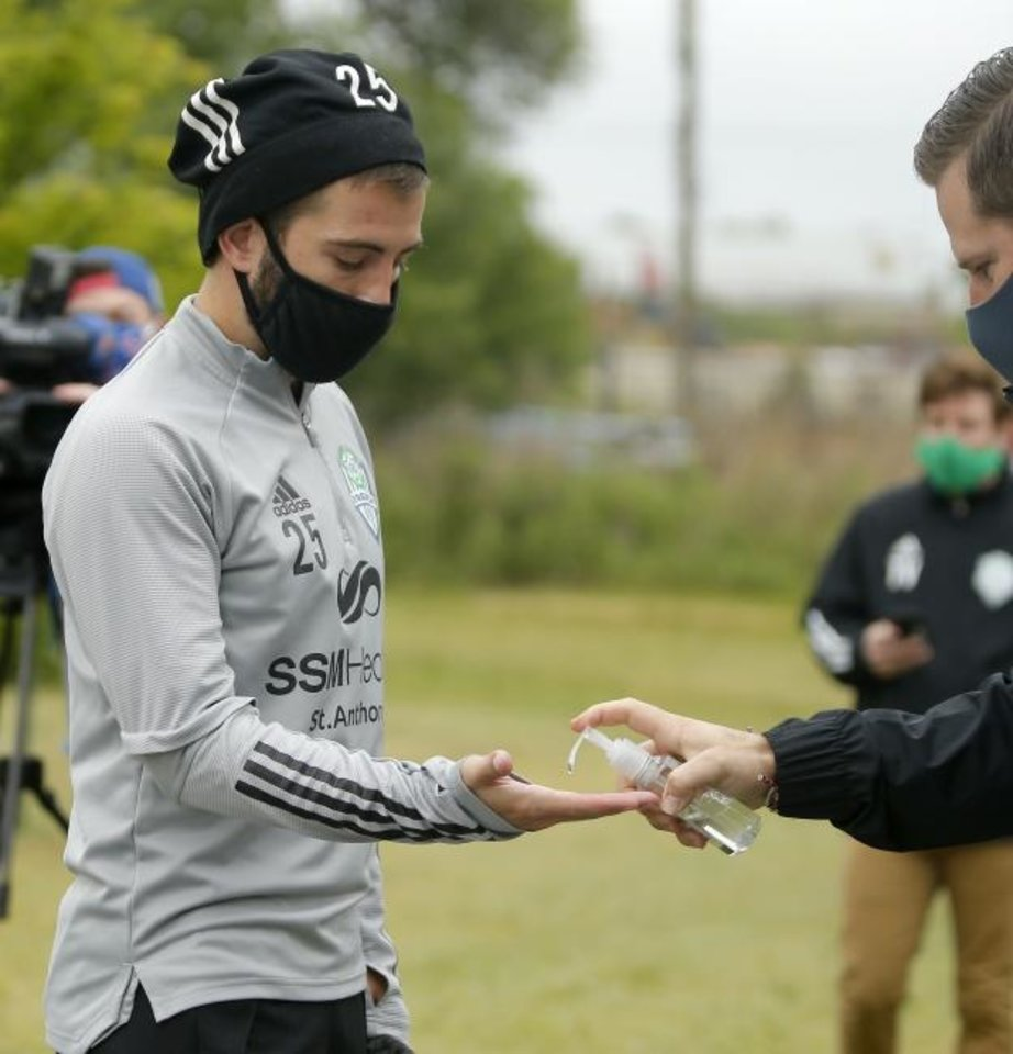 Photo -  Ray Saari with OKC Energy FC is given hand sanitizer as he arrives for soccer practice on Wednesday. [Bryan Terry/The Oklahoman]