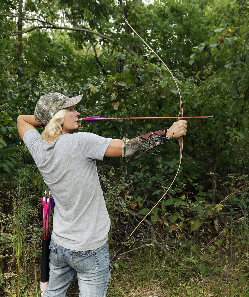 Photo -  Lori Patterson of the Backwoods Bowhunters practices with her bow Thursday on the club's 3D archery range. [PHOTO BY NATE BILLINGS, THE OKLAHOMAN]