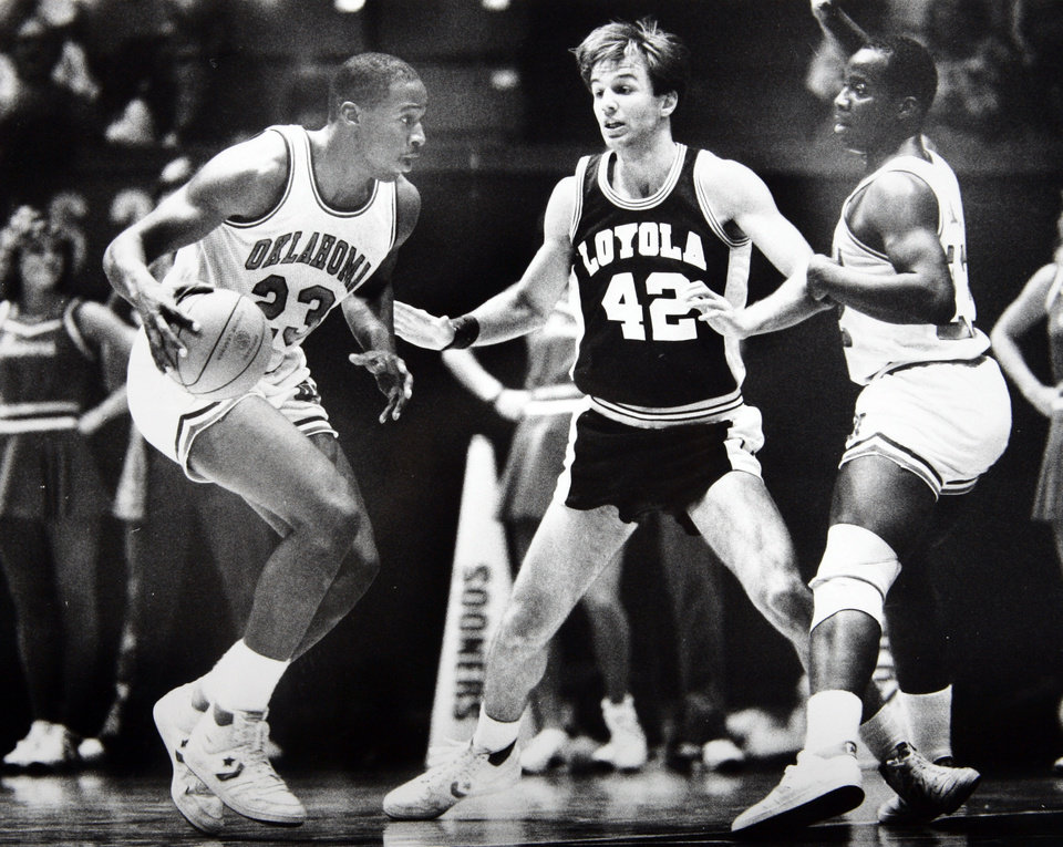Photo - Former OU basketball player Wayman Tisdale. To no  one's surprise, Wayman Tisdale (23) has been unstoppable this year. Loyola's Dave Klusendorf finds out why as OU's William Tisdale paves the way to the basket by setting a pick. Staff photo by Doug Hoke. Photo taken 12/8/1984, Photo published 12/13/1984 in The Daily Oklahoman. ORG XMIT: KOD