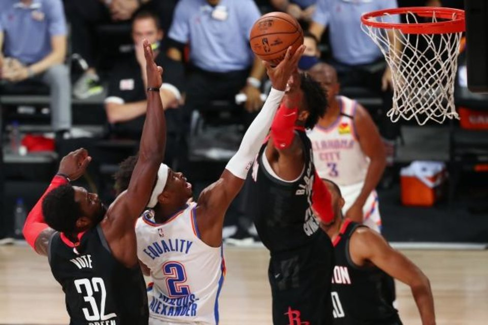 Photo -  Aug 24, 2020; Lake Buena Vista, Florida, USA; Oklahoma City Thunder guard Shai Gilgeous-Alexander (2) shoots against Houston Rockets forward Jeff Green (32) and forward Robert Covington (33) during the second half in game four of the first round of the 2020 NBA Playoffs at AdventHealth Arena. Mandatory Credit: Kim Klement-USA TODAY Sports