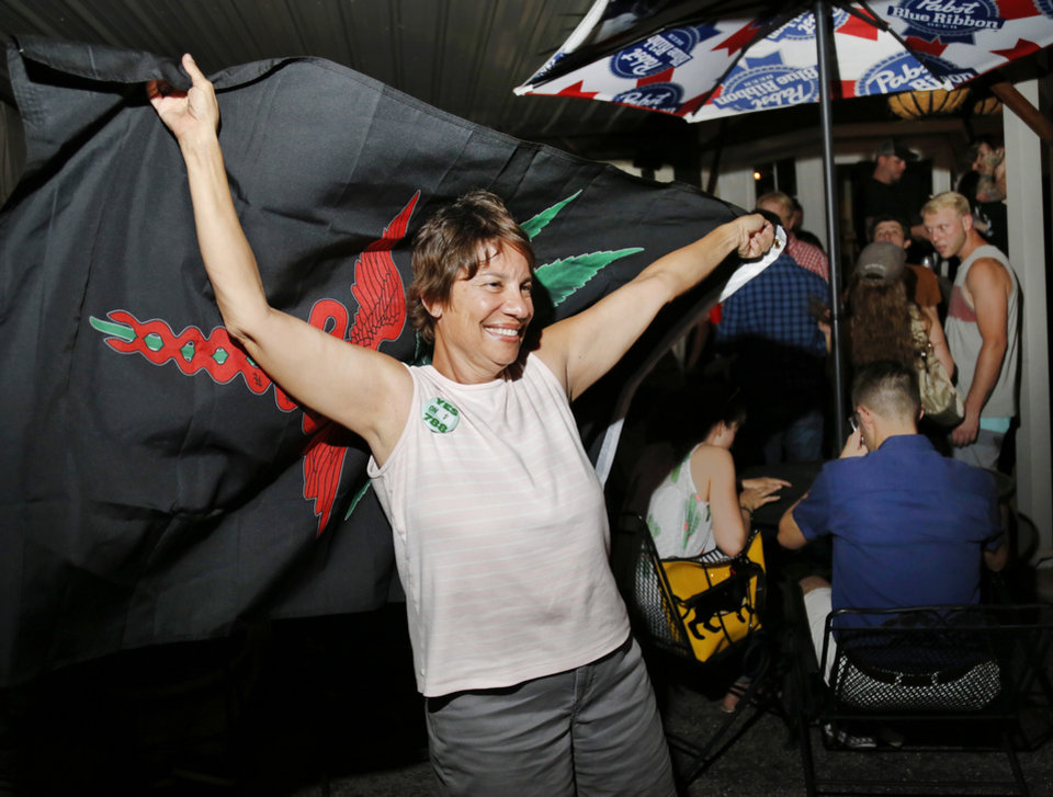 Photo - Kimberly Thomas smiles and jubilantly dances on the patio with a medical marijuana flag draped around her. Several hundred supporters of SQ 788 celebrate the passage of the medical marijuana initiative at a watch party Tuesday night, June 26, 2018, at the Speakeasy, near NW 50 and Western Avenue in Oklahoma City. Photo by Jim Beckel, The Oklahoman
