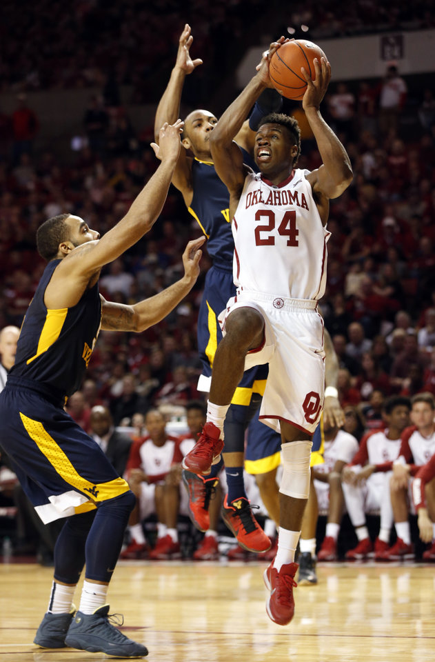 Photo - Oklahoma's Buddy Hield (24) is guarded by West Virginia's Jaysean Paige (5) and Jevon Carter (2) as the University of Oklahoma Sooner (OU) men defeat the West Virginia Mountaineers (WV) 70-68 in NCAA, college basketball at The Lloyd Noble Center on Jan. 16, 2016 in Norman, Okla. Photo by Steve Sisney, The Oklahoman
