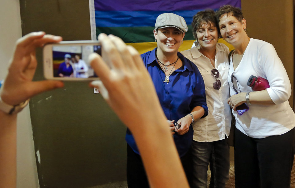 Photo - Jonnette Lynn, Teresa Lynn and Kathy Carson, from left, pose for a photo during a celebration rally at the Cimarron Alliance Equality Center for the U.S. Supreme Court's rulings that stuck down the federal Defense of Marriage Act on Wednesday, June 26, 2013 in Oklahoma City, Okla.  Teresa Lynn and Carson were married in Iowa 13 years ago. The Court's 5-4 decision killed the section of the Defense of Marriage Act that prevented the federal government from recognizing same-sex marriages. Photo by Chris Landsberger, The Oklahoman