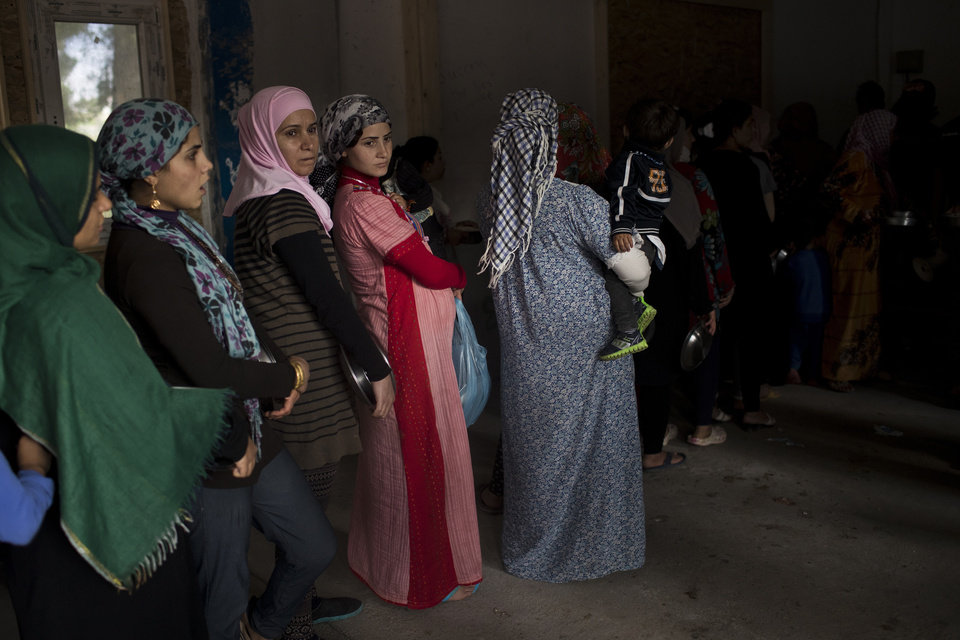 Photo -  FILE - In this Monday, May 29, 2017 file photo, Syrian women queue for food distribution at the refugee camp of Ritsona about 86 kilometers (53 miles) north of Athens. The head of the U.N. food agency warned of starvation and another wave of mass migration from Syria to Europe unless donors countries step up financial assistance to the war-ravaged country. (AP Photo/Petros Giannakouris, File)